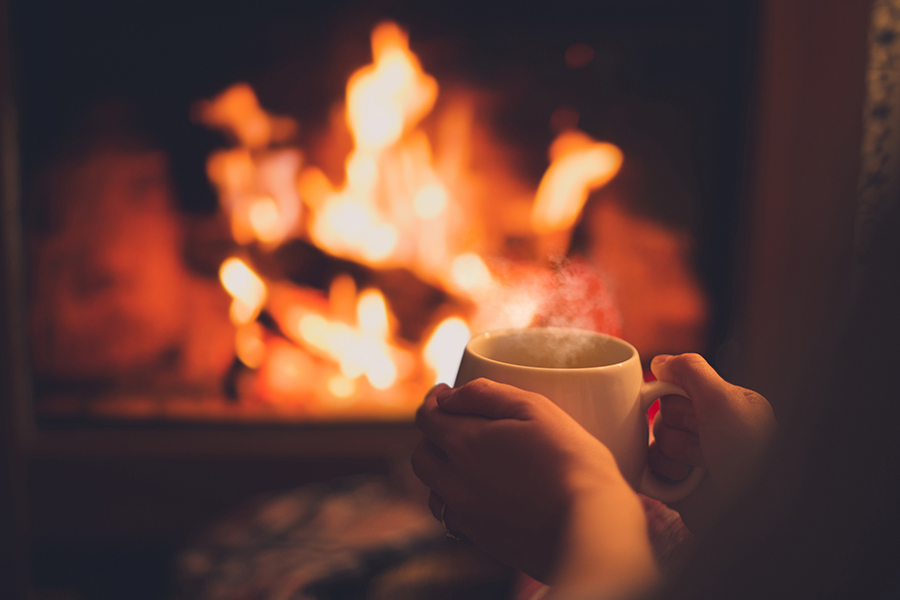 Hot cup of cocoa by a fireplace