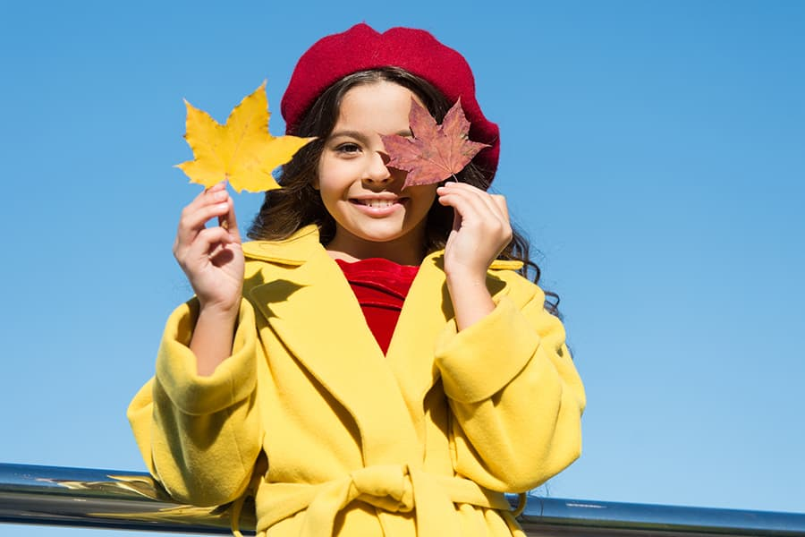 Girl holding maple leaves in Maine