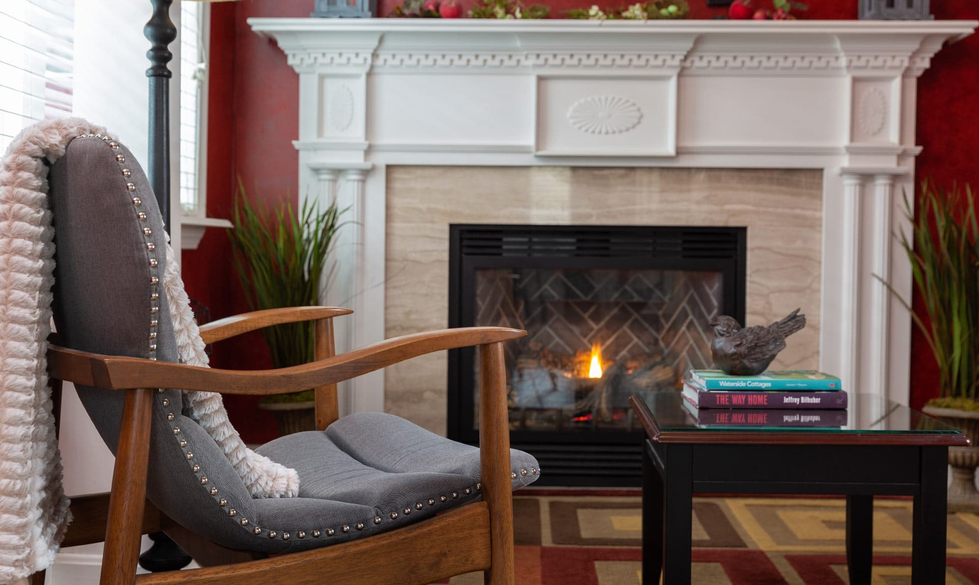 Chair with white blanket next to fireplace at our Camden Inn