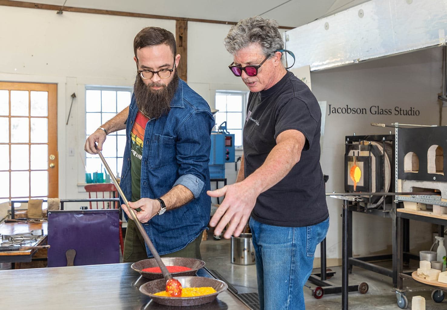 Man teaching another man the art of Glass Blowing