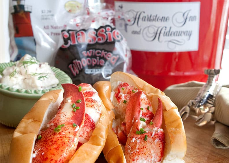 Two lobster sandwiches, red pail in background, and potato chips