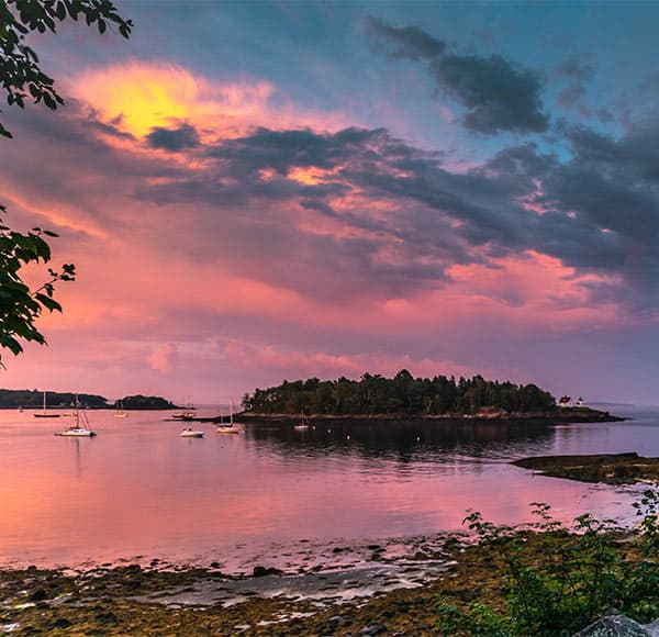 Sunset in Maine with sailboats and lighthouse in distance