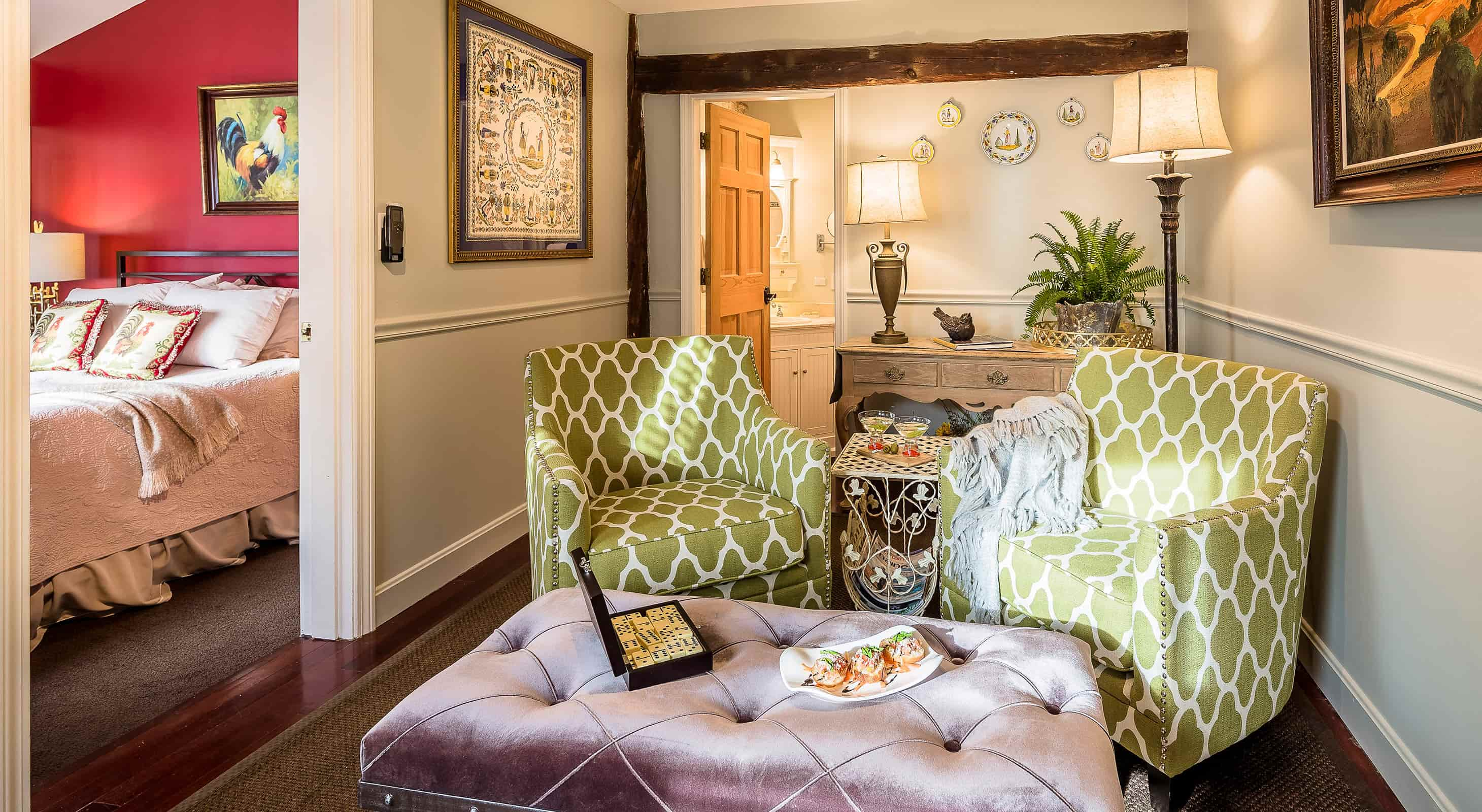 Green and white chairs with lavender ottoman in a sitting room, with bedroom off to side
