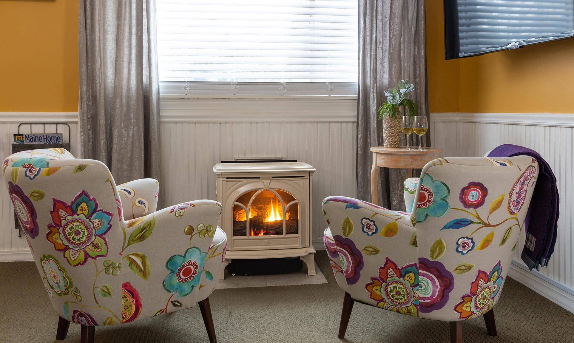 Two colorful chairs in front of fireplace