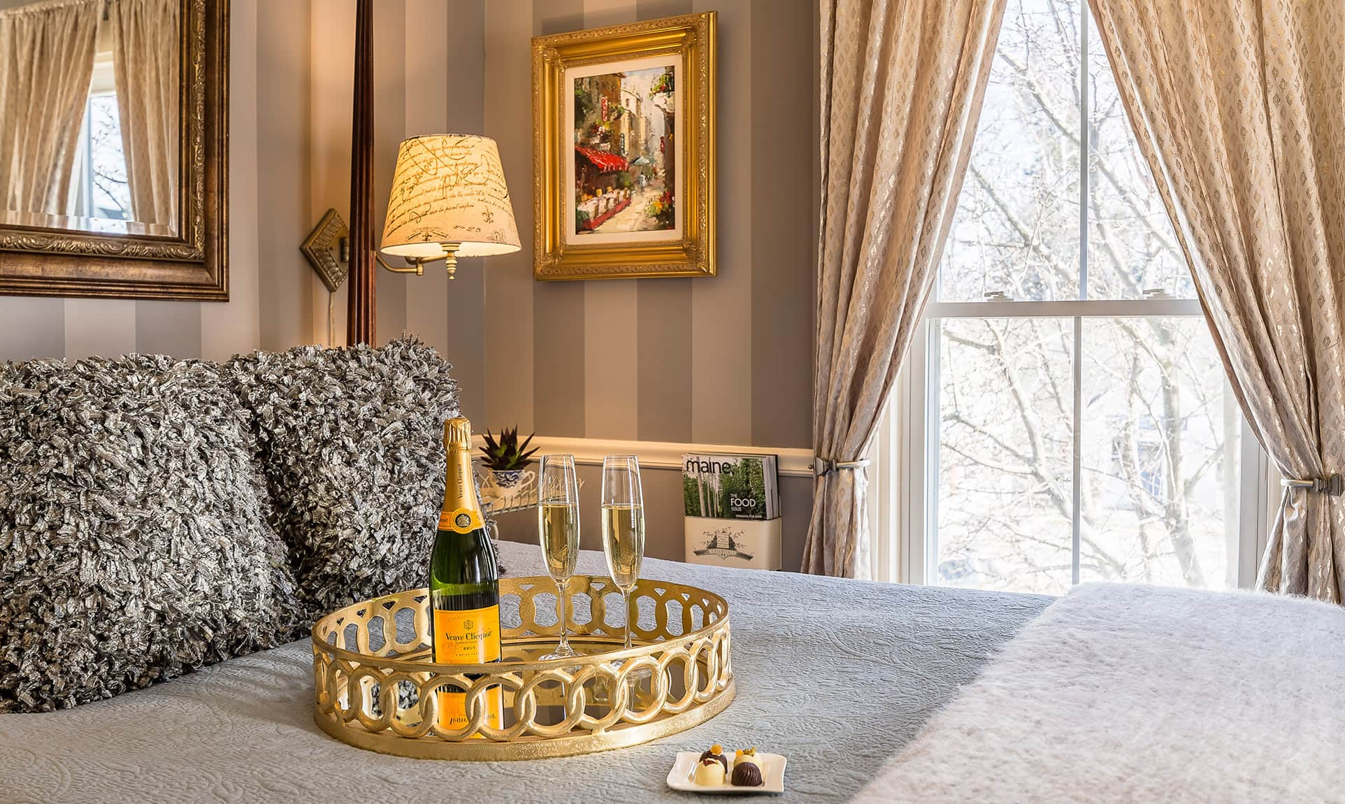 Champagne bottle and glasses on bed