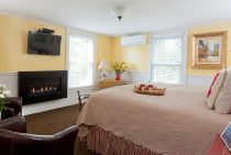 Bed, fireplace, and chairs in Rose Hip Suite