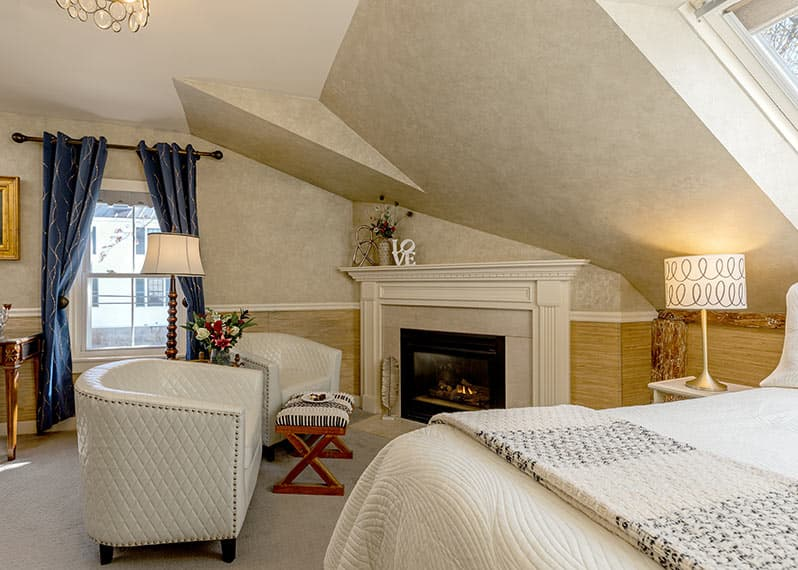 Bed with skylight above and fireplace in The Loft