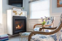 Two chairs in front of the fireplace and TV at our coastal Maine bed and breakfast